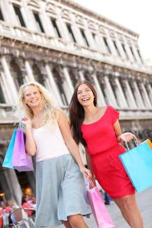 Women shopping happy holding shopping bags walking having fun laughing. Two beautiful young Asian woman and Caucasian woman girlfriends on travel vacation, Piazza San Marco Square, Venice, Italy photo