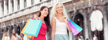 marco: Shopping women banner. Happy shoppers holding shopping bags having fun laughing. Two beautiful young Asian and Caucasian woman girlfriends on travel vacation, Piazza San Marco Square, Venice, Italy Stock Photo