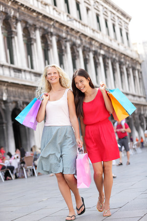 Shopping women walking happy holding shopping bags having fun laughing. Two beautiful young Asian woman and Caucasian woman girlfriends on travel vacation, Piazza San Marco Square, Venice, Italy photo