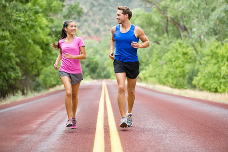 Running - exercising couple jogging and talking outside on road beautiful nature landscape.  Stock Photo