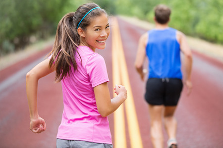 Woman runner smiling looking at camera. Couple running together training outdoors on red road in summer. Beautiful young multiracial Asian Caucasian female fitness sports model. photo