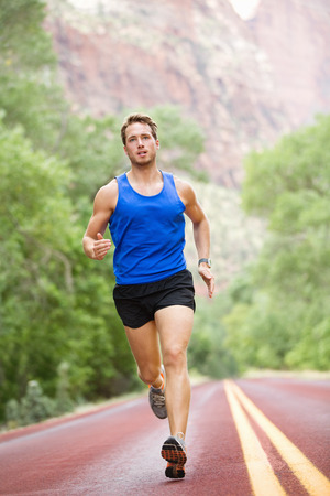 Runner - running athlete man. Male sprinting during outdoors training for marathon run.