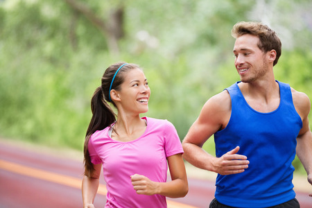 Healthy lifestyle - Running fitness couple jogging laughing, talking outside on road in beautiful nature.  photo