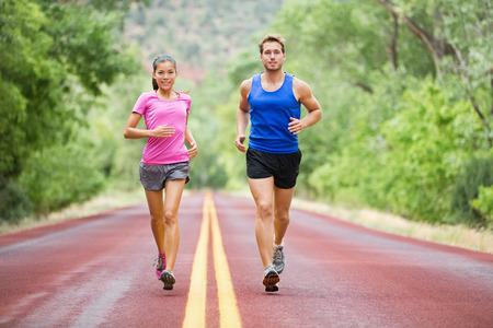 Fitness sport couple running jogging outside on road beautiful nature landscape.