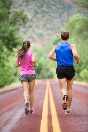espalda: Ejecuci�n de los corredores de entrenamiento para correr en carretera fuera de la vista trasera de huir de la c�mara en la naturaleza del paisaje. Foto de archivo