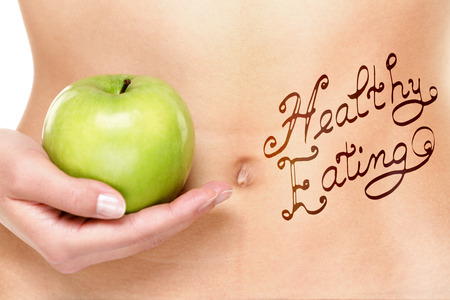 Healthy eating concept - woman stomach and apple. photo