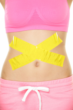 celiac: Stomach pain health digestion problems concept with tape crossed over woman belly. Take care of your body, food poisoning or other concept. Conceptual healthy lifestyle image. Stock Photo
