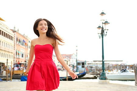 Woman happy running in summer dress, Venice, Italy.