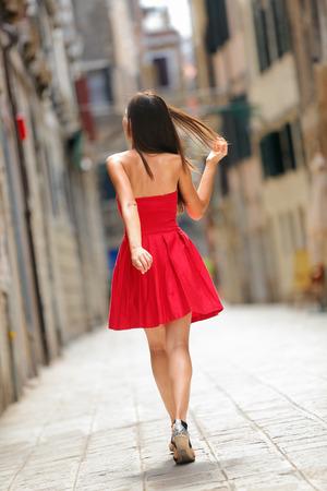 Vrouw in rode jurk lopen in de straat in Venetië, Italië vrolijk en gelukkig in achteraanzicht toont achterkant van zomerjurk.