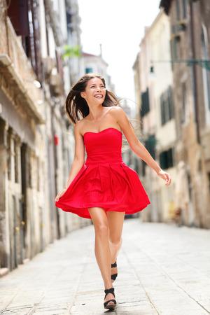 赤いサマードレス歩行・走行うれしそうな、陽気なヴェネツィア、イタリアで笑顔で幸せな美しい女性。彼女の 20 代の非常にセクシーなファッショ 写真素材