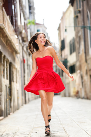 Happy beautiful woman in red summer dress walking and running joyful and cheerful smiling in Venice, Italy. Pretty sexy fashion model girl in her 20s. Mixed race Asian Caucasian female model outside. photo