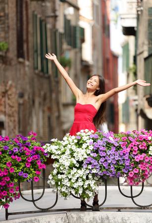 Woman happy in romantic Venice, Italy Girl standing in summer dress on bridge with flowers smiling joyful having fun. photo