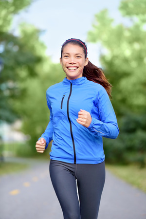 Happy woman runner healthy lifestyle concept with girl jogging smiling training outside in park for marathon.  photo
