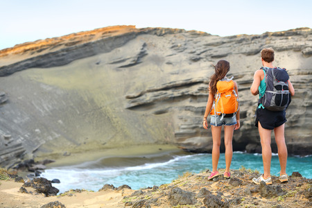 backpacking: Hikers - travel couple tourists hiking on Hawaii. Tourist backpackers walking on Green Sand Beach, Papakolea on Big Island, Hawaii, USA. Young happy couple traveling with backpacks. Stock Photo