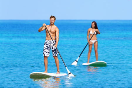 Paddleboard beach people on stand up paddle board surfboard surfing in ocean sea on Big Island, Hawaii Beautiful young multi-ethnic couple, mixed race Asian woman and Caucasian man doing water sport. photo