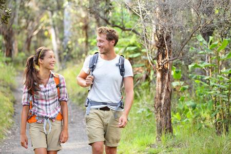 Wandelaars - wandelen mensen lopen gelukkig in het bos. Wandelaar paar lachen en glimlachen. Interracial paar, blanke man en Aziatische vrouw op Big Island, Hawaii, USA. Stockfoto