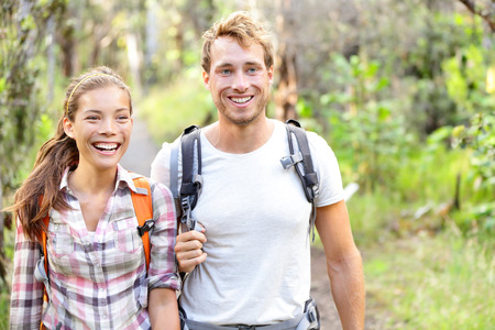 Hiking - hikers walking happy in forest. Hiker couple laughing and smiling. Interracial couple, Caucasian man and Asian woman on Big Island, Hawaii, USA. photo
