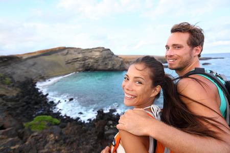 Hiking - travel couple tourist on Hawaii hike. Tourist backpackers walking on Green Sand Beach, Papakolea on Big Island, Hawaii, USA. Interracial young happy couple traveling with backpacks.