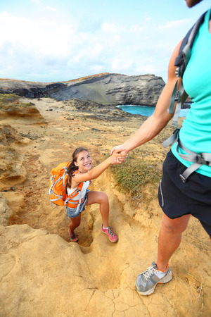 Help - hiker woman getting helping hand hiking on hike smiling happy. Tourist backpackers walking on Green Sand Beach, Papakolea on Big Island, Hawaii, USA. Young couple traveling with backpacks.