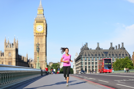 London lifestyle woman running near Big Ben. Female runner jogging training in city with red double decker bus. Fitness girl smiling happy on Westminster Bridge, London, England, United Kingdom. photo