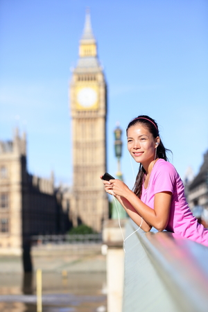 London woman runner listening to music on smartphone near Big Ben. Female running girl resting after training in city. Fitness girl smiling happy on Westminster Bridge, London, England, United Kingdom photo