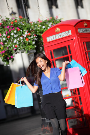 London shopper girl happy excited holding shopping bags by red phone booth. Woman shopping smiling in London, England, United Kingdom during spring or summer. Mixed race Asian Caucasian model. photo