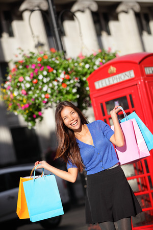 London shopping woman happy excited holding shopping bags by red phone booth. Female shopper smiling in London, England, United Kingdom during spring or summer. Multicultural Asian Caucasian model. photo