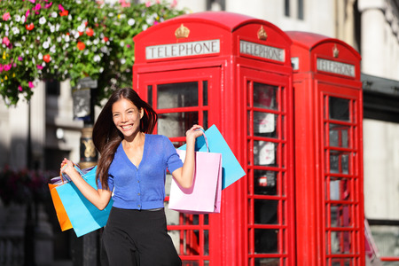 England London shopping woman shopper holding shopping bags by red phone booth. Female shopper smiling in London, England, United Kingdom during spring or summer. Mixed race Asian Caucasian model. photo