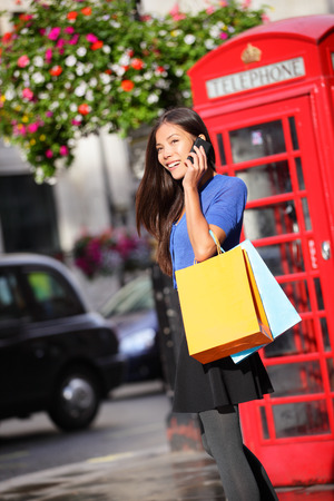 cell phone booth: London woman talking happy on smartphone shopping holding shopping bags by red phone booth. Female shopper using mobile smart phone smiling in London, England, United Kingdom. Mixed Asian Caucasian.