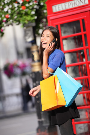 London woman talking happy on smart phone shopping while laughing on mobile phone holding shopping bags by red phone booth. Female shopper smiling in London, England, United Kingdom. Mixed race Asian. photo