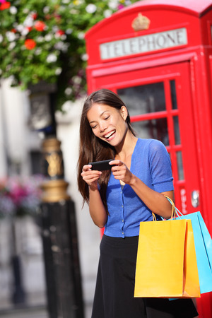 London woman on smart phone shopping texting on mobile phone holding shopping bags by red phone booth. Female shopper smiling in London, England, United Kingdom during spring or summer. photo
