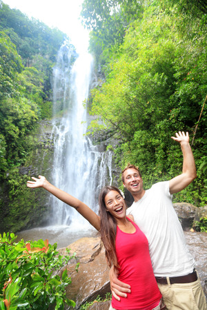 Hawaii tourist people couple happy by waterfall during travel on the famous road to Hana on Maui, Hawaii. Ecotourism concept image with happy backpackers. Interracial Asian  Caucasian young couple. photo