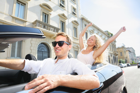 Car people - man driving with happy woman. Male driver wearing sunglasses. Young couple having fun in car driving on travel vacation together. Lifestyle with beautiful cheerful lovers. photo