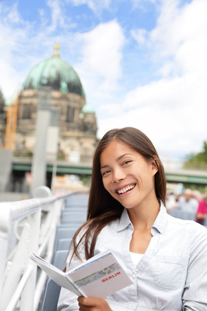 guidebook: Asian tourist woman on boat tour Berlin, Germany having fun smiling happy while enjoying mini cruise reading guidebook. Europe travel vacation holiday concept. Multiracial Asian Caucasian woman.