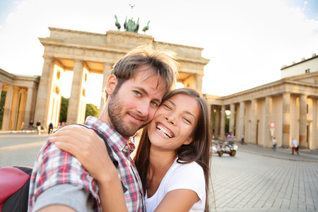 Happy couple selfie selfportrait in front of Brandenburg Gate or Brandenburger Tor, Berlin, Germany. Beautiful young multiracial travel couple having fun on Europe vacation. Asian woman, Caucasian man Stock Photo