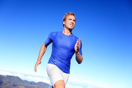 Atleet loper sprinten loopt tot succes. Fit mannelijk fitness sprinter opleiding in de sprint met vastberadenheid en kracht. Knappe atletische man uit te werken buiten op de blauwe hemel.