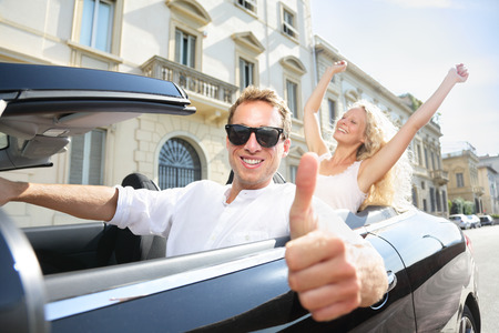 drivers: Car driver happy giving thumbs up - driving couple excited on road trip travel vacation. Male driver wearing sunglasses. Lifestyle with beautiful cheerful lovers, man and woman.