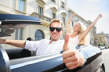 Feliz conductor del coche hasta que los pulgares - conducción pareja emocionada en viajes vacaciones viaje por carretera. Conductor con gafas de sol masculinas. Estilo de vida con hermosos amantes alegres, hombre y mujer. Foto de archivo