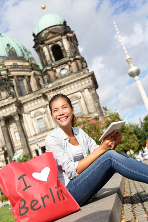 Tourist in Berlin, Germany on travel reading guidebook. Woman sitting with shopping back saying I LOVE BERLIN smiling happy in front Berlin Cathedral  Berliner Dom and Fernsehturm  Berlin TV Tower. Imagens