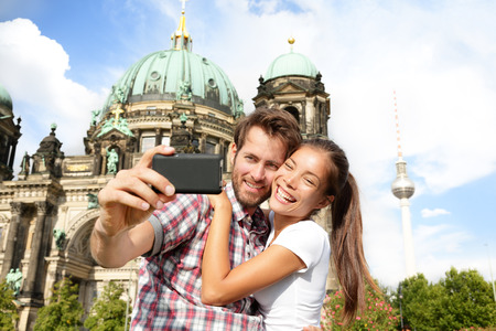 Travel couple selife self portrait, Berlin, Germany. Happy tourists people in front of Berlin Cathedral  Berliner Dom with Fernsehturm  Berlin TV Tower in the background. Asian woman, Caucasian man. Stock Photo
