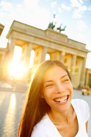 Happy laughing woman at Brandenburg Gate or Brandenburger Tor, Berlin, Germay. Lifestyle with smiling joyful Beautiful mixed race Asian Caucasian girl tourist on travel in Europe. photo