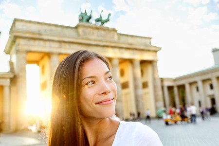 brandenburg: Berlin people - woman at Brandenburg Gate or Brandenburger Tor, smiling happy in Berlin, Germany. Beautiful multiracial Asian Caucasian woman looking to side during travel in Europe. Stock Photo