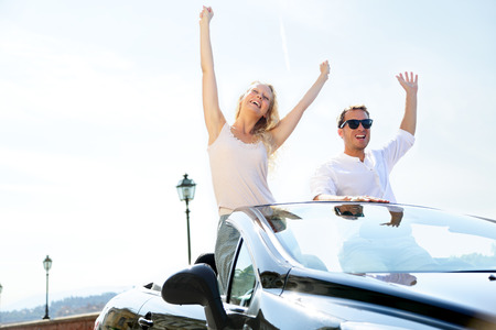 cabriolet: Happy people in car driving on road trip. Young couple having fun dancing and cheering in car driving on travel vacation together. Lifestyle with beautiful cheerful lovers, young woman and man.