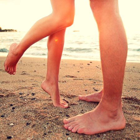 Kissing lovers - couple on beach love concept showing feet in close up. Woman standing on toes to kiss man at sunset during romantic summer holidays vacation. photo