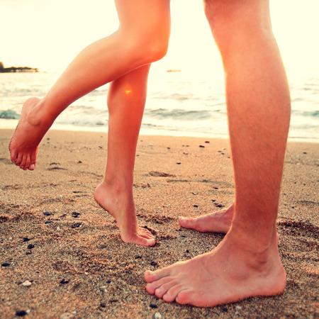 enamorados besandose: Los amantes se besan - pareja en el amor concepto playa mostrando los pies en primer plano. Mujer de pie en puntillas para besar el hombre al atardecer durante romántica vacaciones de verano vacaciones.