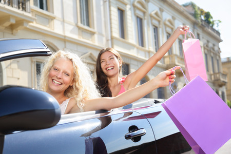 Car driver woman driving and shopping with girl friends holding shopping bags happy and excited on road trip travel vacation in convertible car in summer. Two beautiful women girlfriends shoppers. photo