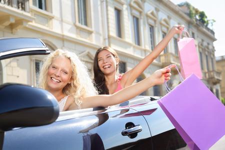 carro supermercado: Mujer que conduce el conductor del coche e ir de compras con amigas con bolsas de compras feliz y emocionado de vacaciones, viaje, viaje por carretera en coche descapotable en verano. Dos mujeres hermosas novias compradores.