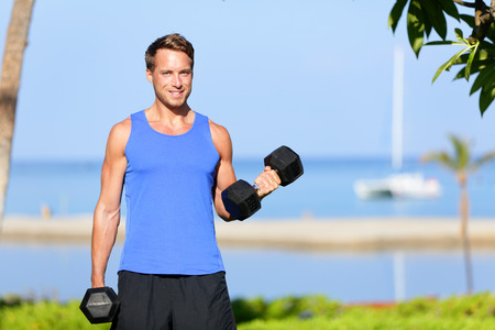 bicep: Fitness bicep curl - weight training man outdoors working out arms lifting dumbbells doing biceps curls. Male sports model exercising outside as part of healthy lifestyle. Stock Photo