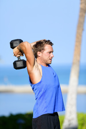 Fitness man lifting dumbbells training triceps doing overhead dumbbell extensions outdoors in summer. Fit muscular sport model strength training lifting weights outside.