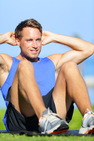 situps: Man doing sit-ups outdoor. Male fitness model training sit up exercise during outside workout in grass in summer. Handsome muscular male sport model working out. Stock Photo